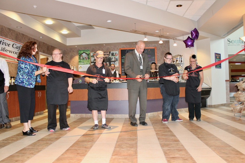 A picture of the creative living coffee team cutting the ribbon for the ribbon cutting ceremony for their creative cafe