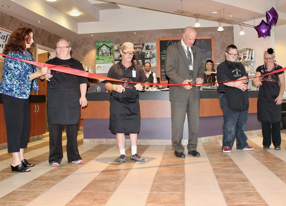 picture of the the ribbon cutting for the creative living coffee with abled individuals helping cut the ribbon