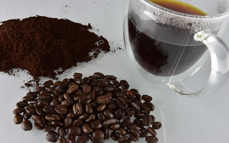 picture of some brazilian road coffee beans next to some coffee grounds and a cup filled with brazilian road coffee