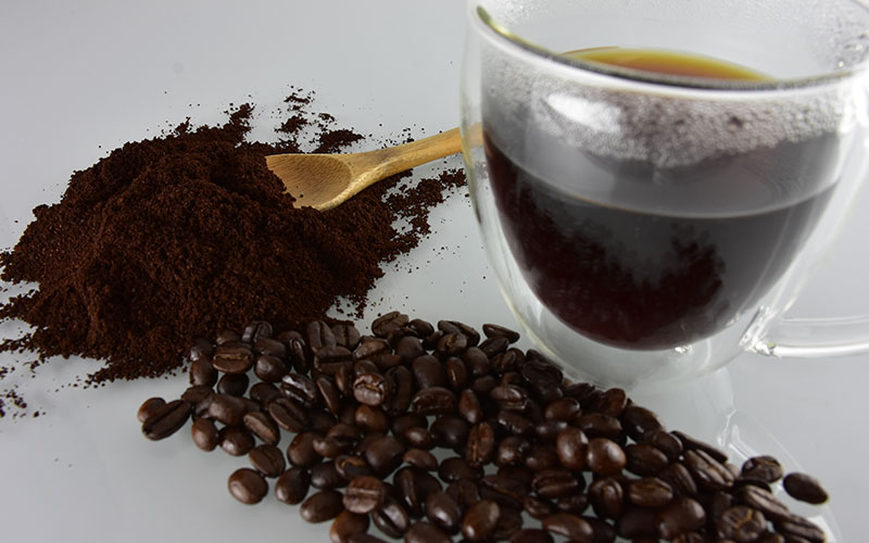 picture of creative colombian bold supreme coffee grounds and coffee beans with a wooden spoon and cup of creative colombian bold supreme coffee