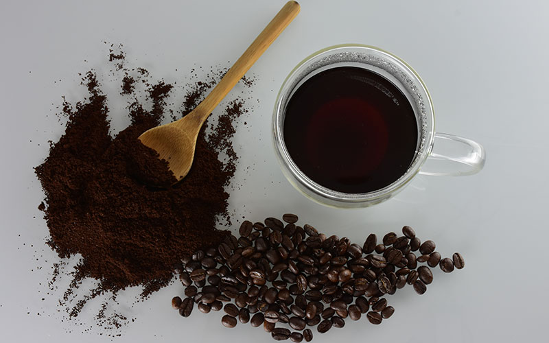 picture of creative colombian bold supreme coffee beans and grounds with a wooden spoon in the grounds and a cup of colombian bold supreme coffee