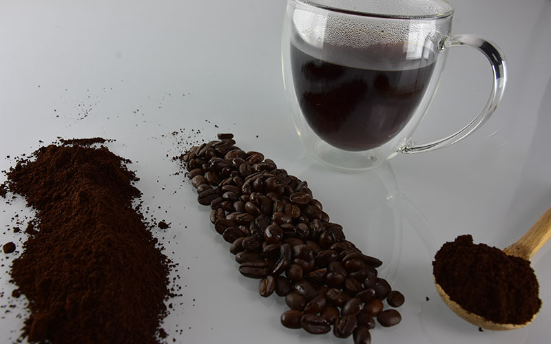 picture of creative premium decaf coffee grounds and coffee beans with a wooden spoon with coffee grounds on it and a cup of creative premium decaf coffee