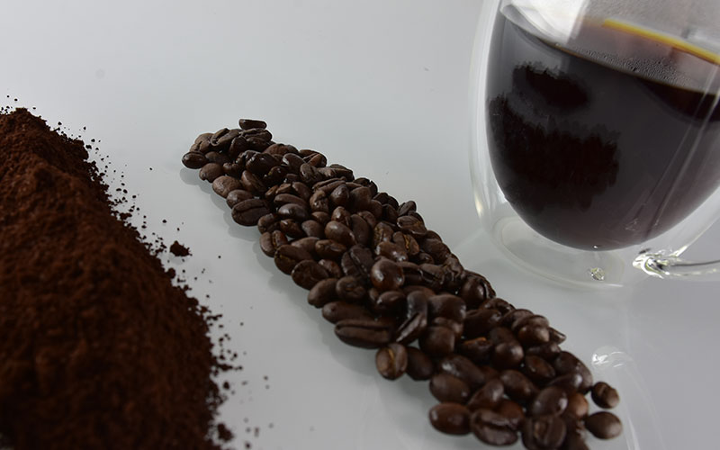 picture of creative premium Jamaican blue mountain coffee grounds and coffee beans with a cup of creative premium decaf coffee in the background