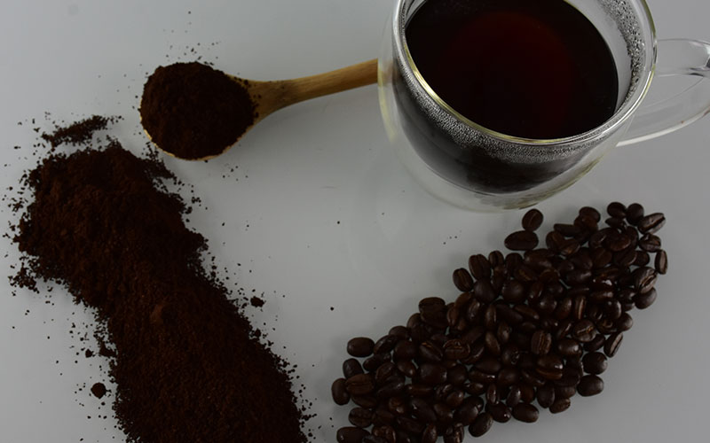 ppicture of coffee beans with grounds and a spoon with coffee grounds on it and a coffee cup filled with java jubilee coffee in the top corner