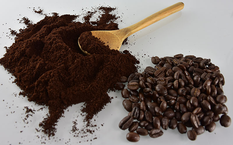 picture of ground italian dark roast coffe with coffee beans and a wooden spoon on a white background