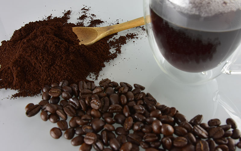 picture of italian dark roast coffee beans and grounds with a wooden spoon and a cup with italian dark roast coffee in it