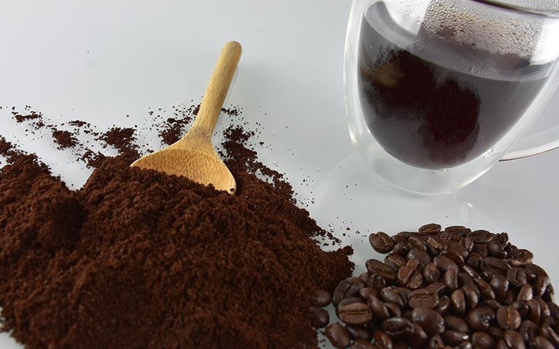 picture of meximala coffee grounds and coffee beans with a cup of meximala coffee in the background