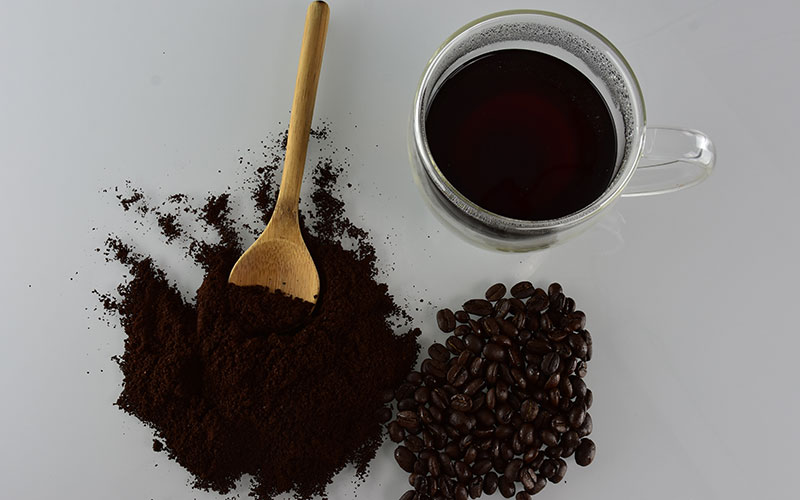 picture of a coffee cup with java jubilee coffee in it and coffee beans with coffee grounds next to it and a wooden spoon laying in the coffee grounds
