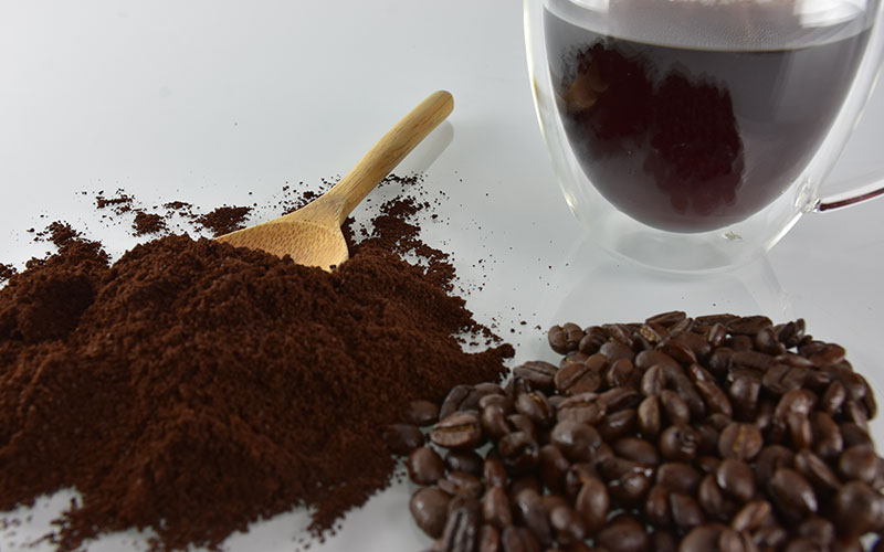 picture of coffee beans and coffee grounds in the foreground with a spoon and coffee cup in the background for creative living coffee house blend