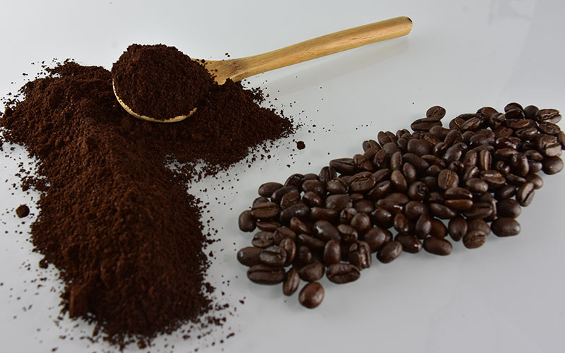 picture of coffee beans and coffee grounds with a wooden spoon in the coffee grounds of sumatran smooth coffee