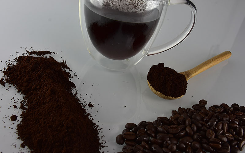 picture of a coffee cup with a spoon in the center with coffee grounds on it and some coffee beans in the corner for creative living coffee house blend coffee